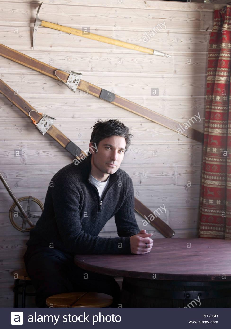man sitting at ski lodge table - Stock Image