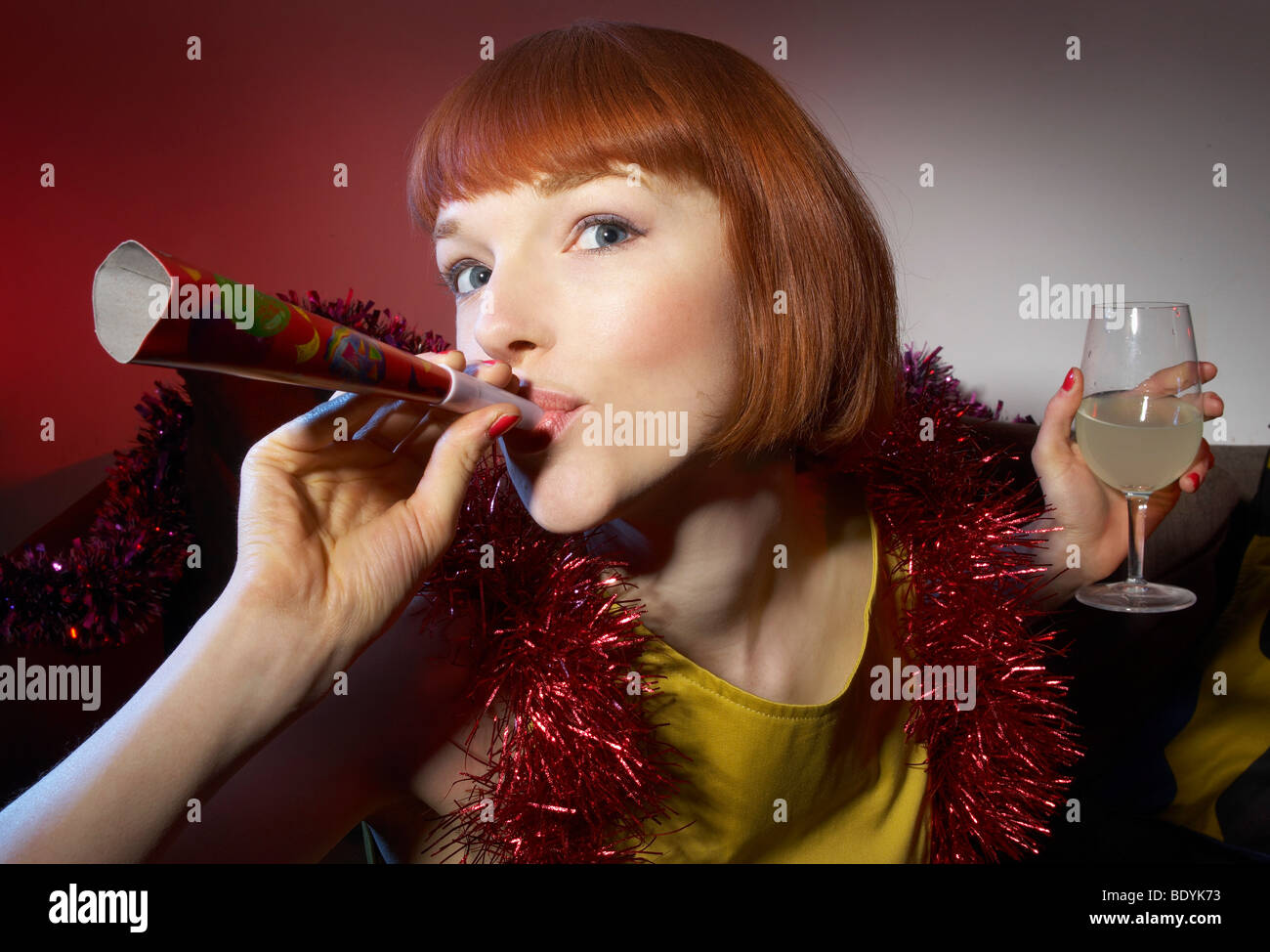 woman at party blowing party horn blower - Stock Image