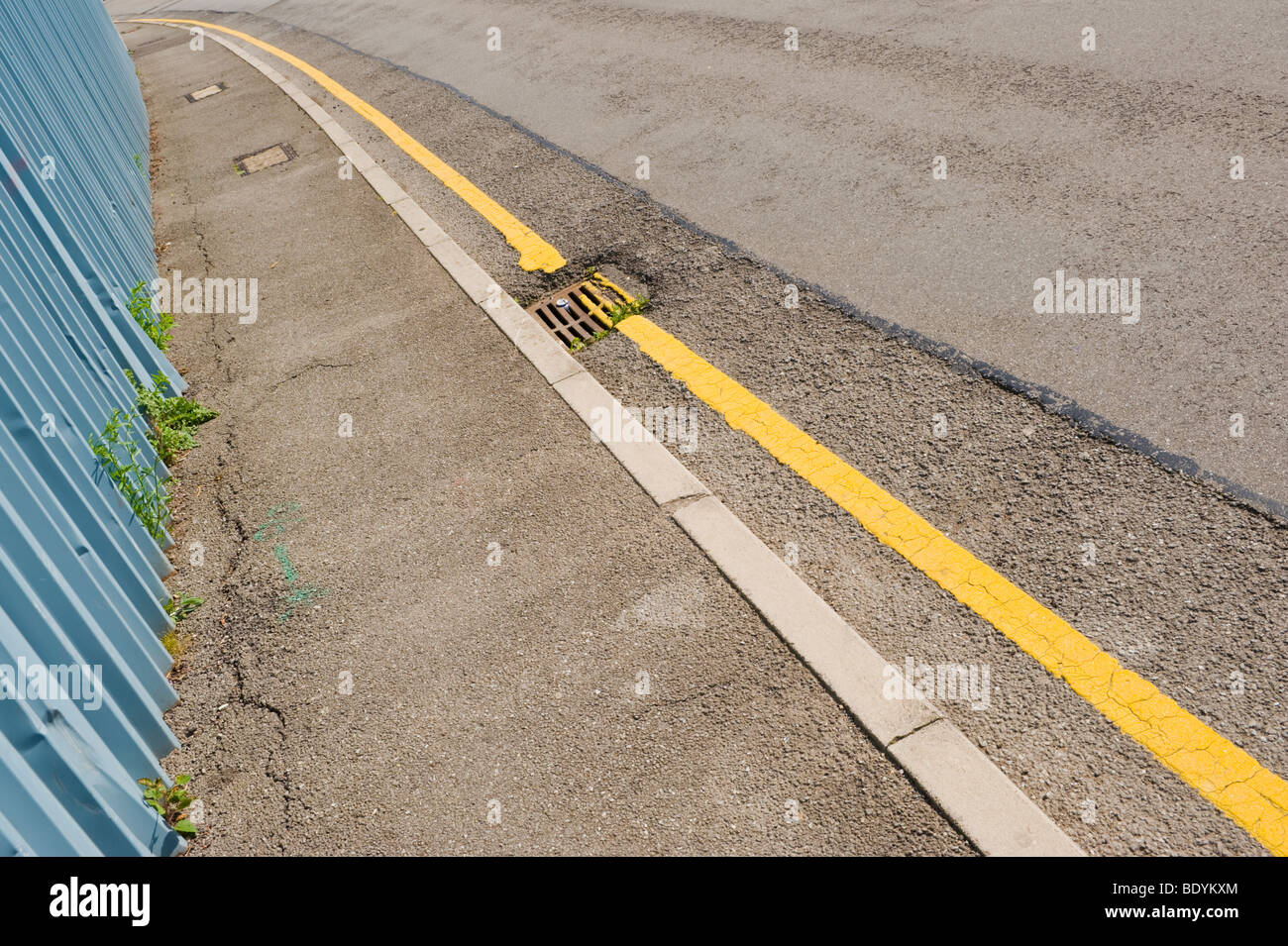 Yellow line parking restriction painted on road UK - Stock Image