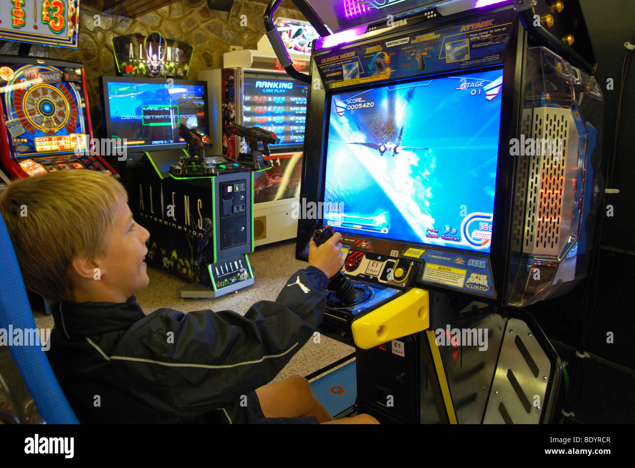 a young boy playing on a computer simulated war game in an amusment arcade in blackpool,england,uk - Stock Image