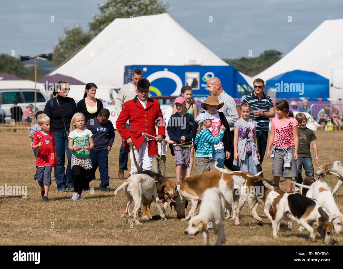 A huntsman walking with his pack of hounds accompanied by children and adults.  Photo by Gordon Scammell.  Photo - Stock Image