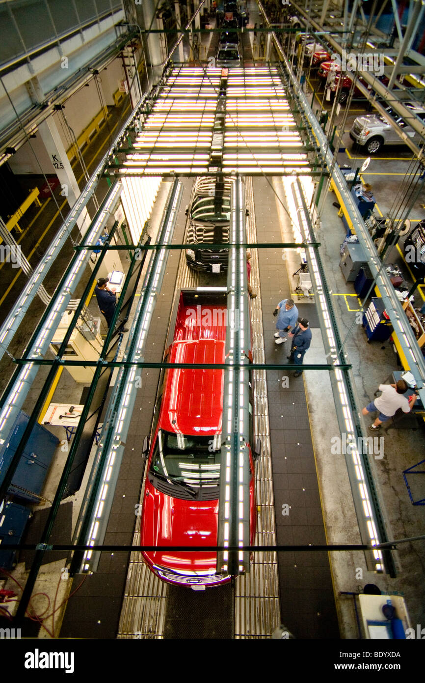 Completed F-150 pickup trucks move down the production line through the bright lights of final inspection at the - Stock Image
