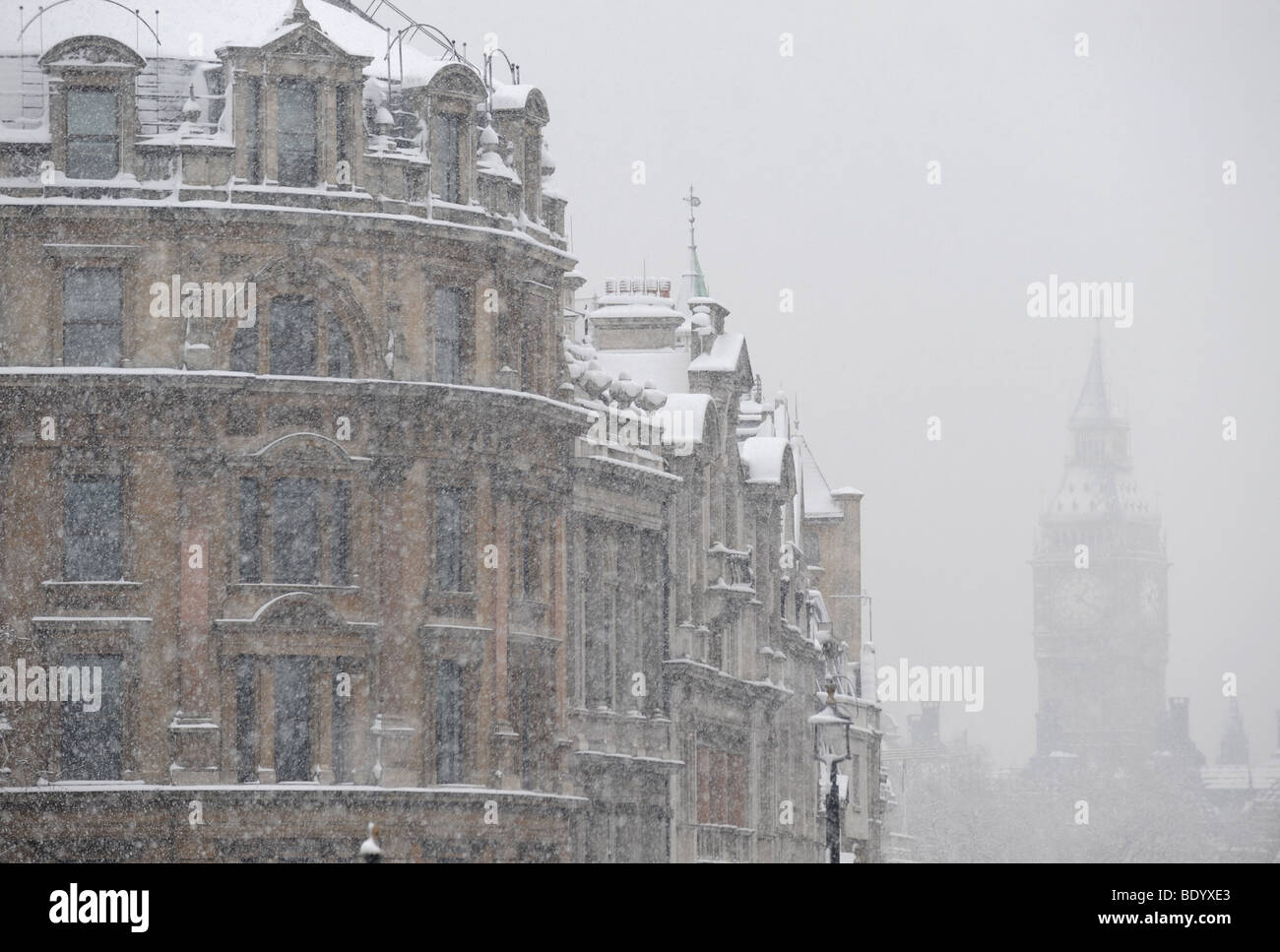 View from Trafalgar square down Whitehall to Houses of Parliament obscured by heavy snow. - Stock Image