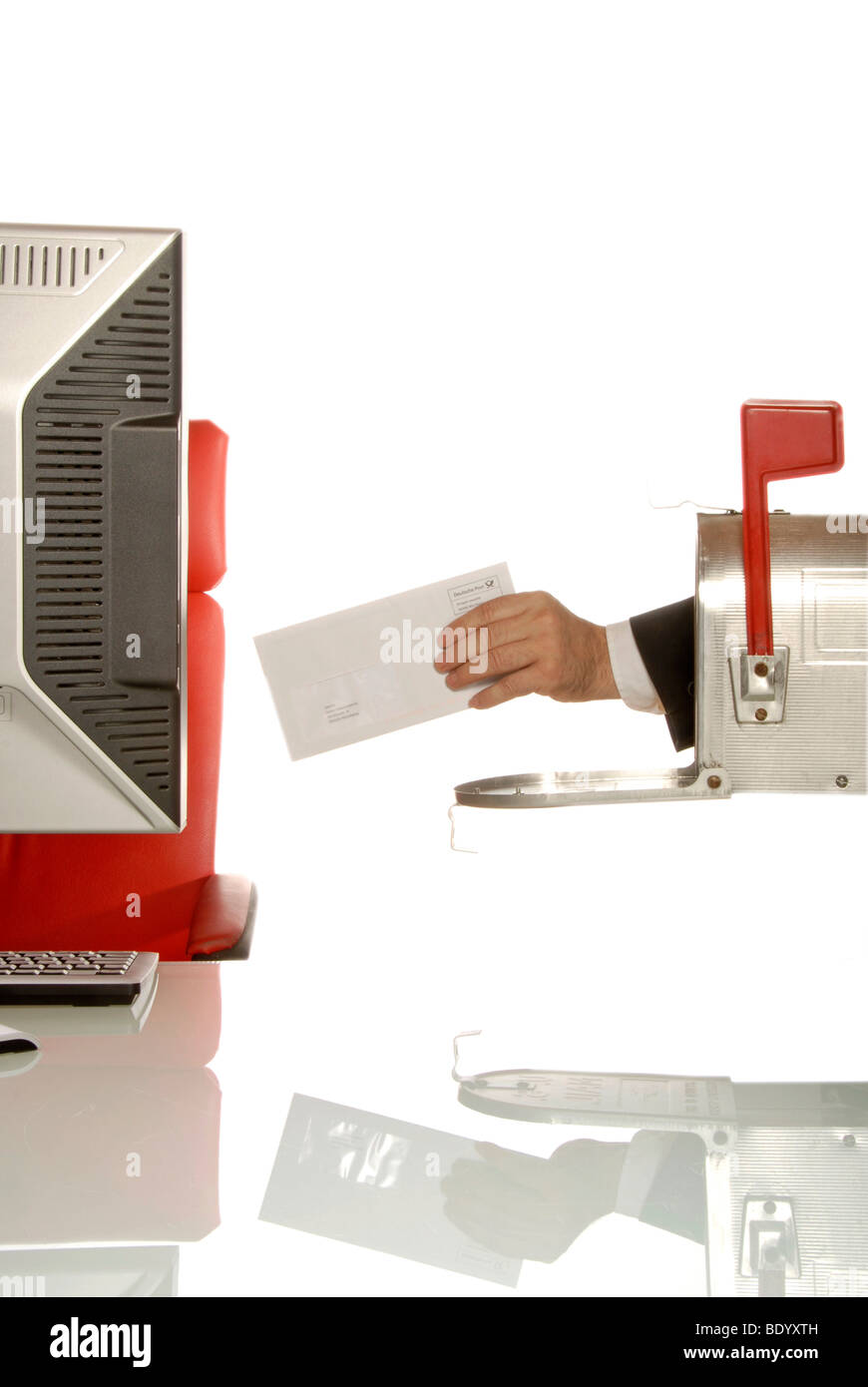 Hand holding a letter coming out of a U.S. mailbox and passing it towards a computer work station - Stock Image