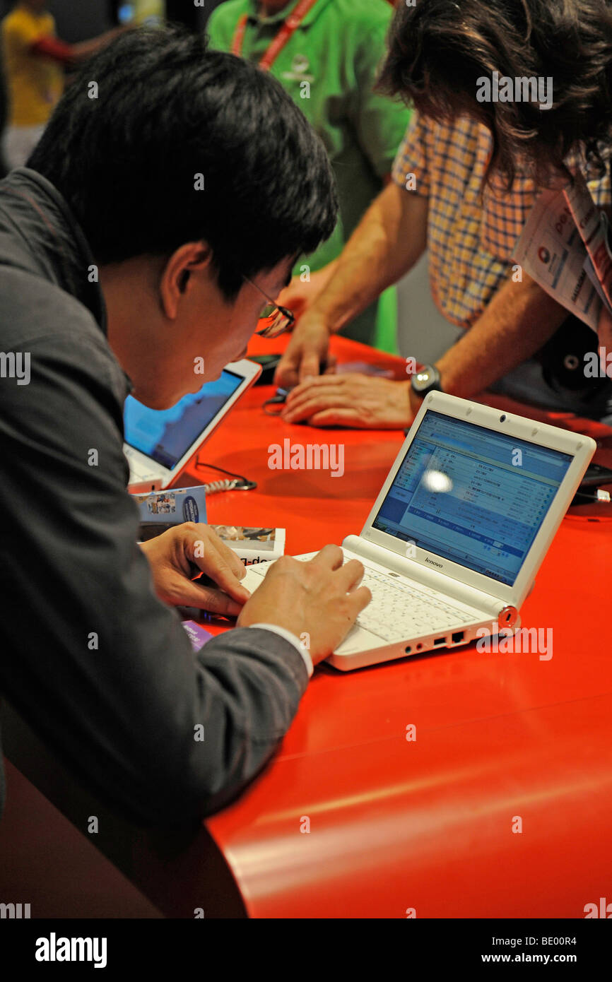 Visitor interested in a mini-notebook, netbook, at the IFA Internationale Funkaustellung consumer electronics fair - Stock Image
