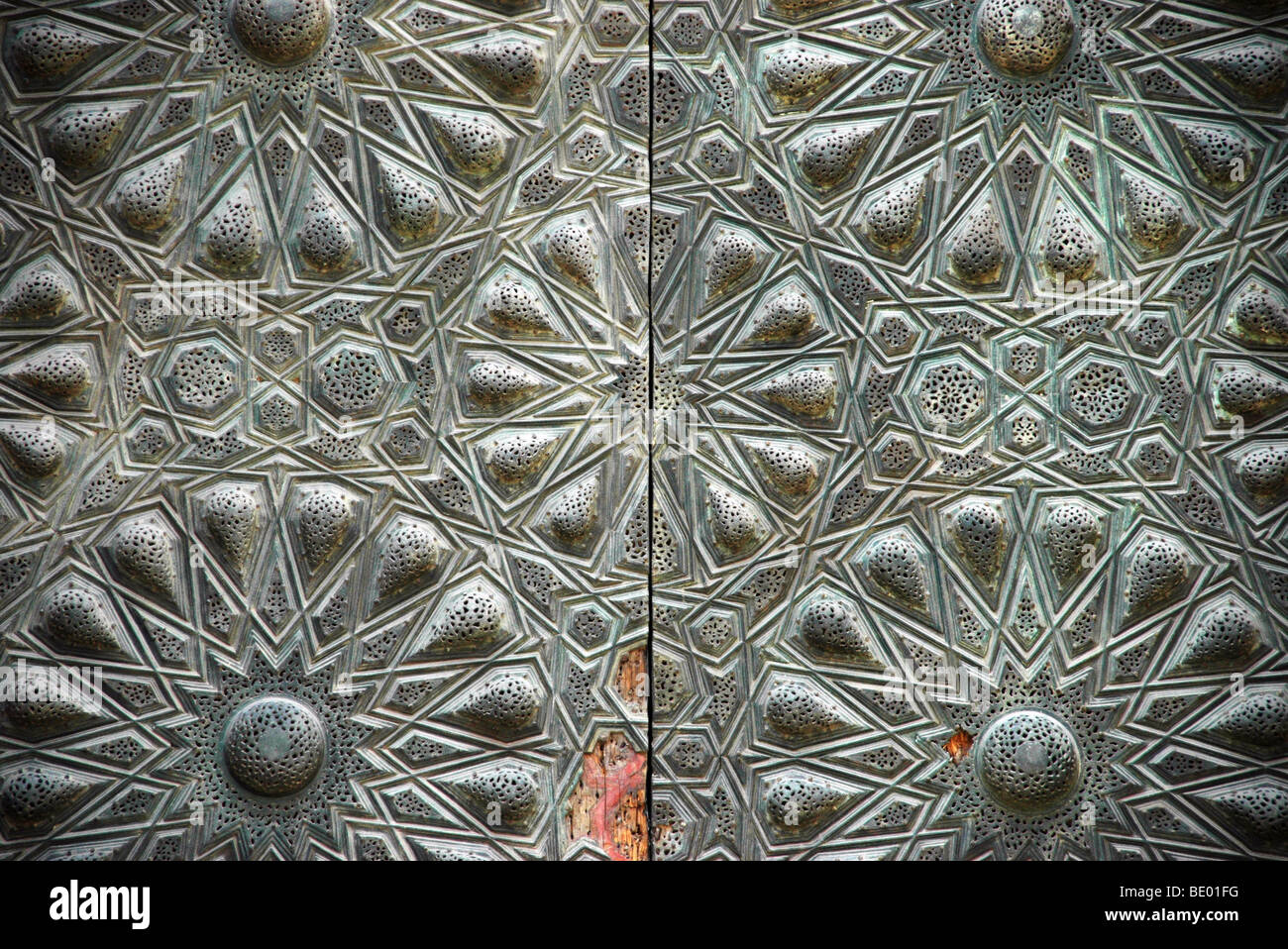 Metallic bronze Islamic geometric motifs on a wooden door in the Mosque of Sultan al-Muayyad in the medieval quarter - Stock Image