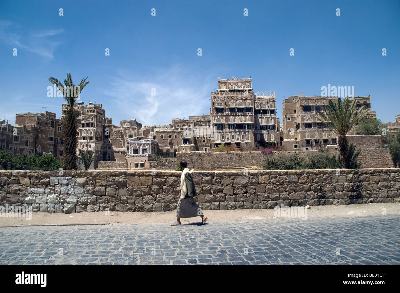 A man strolling past tower houses in a pedestrian area of the old city of Sana'a, Yemen. - Stock Image