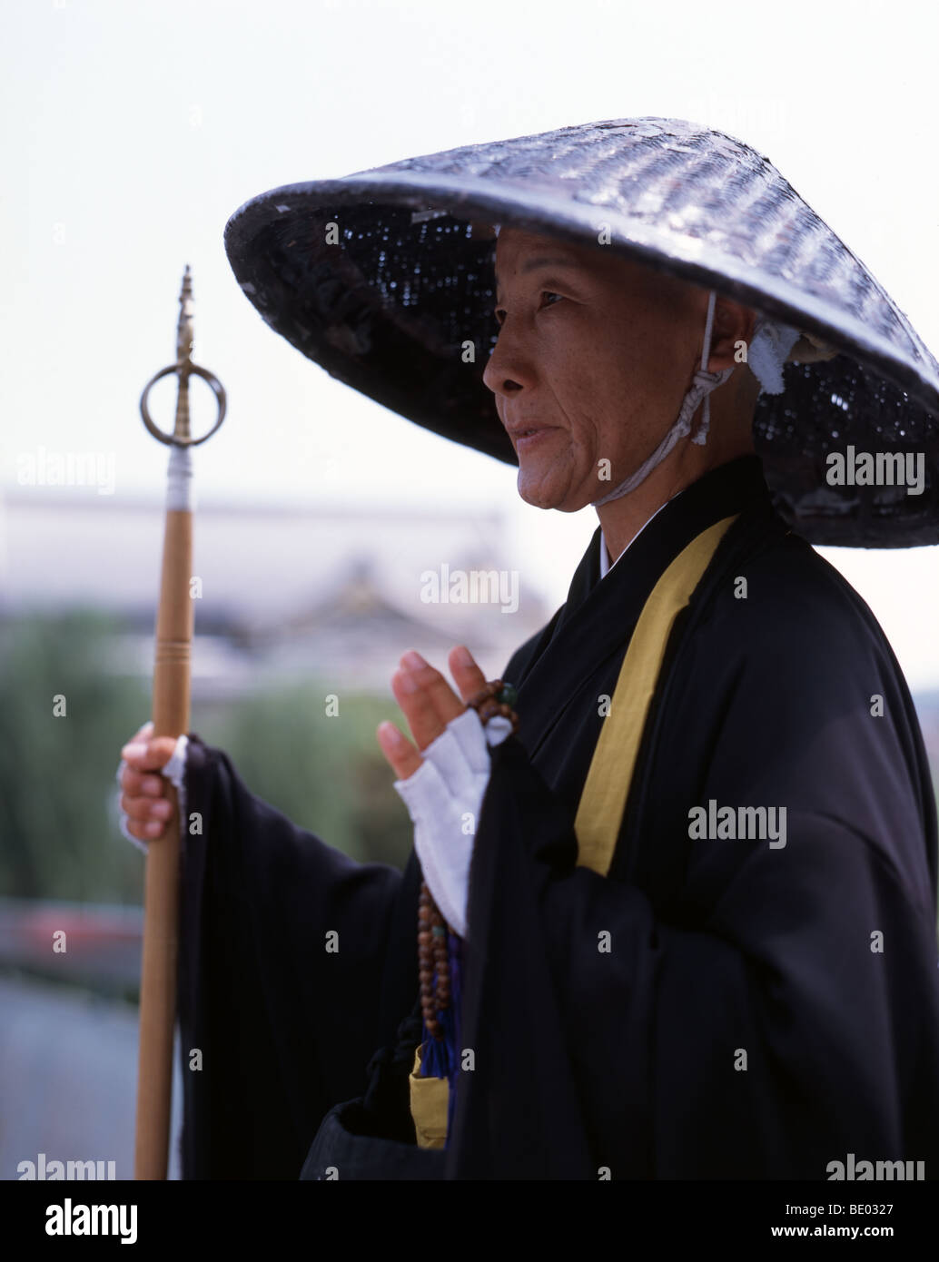 Female monk in Kyoto, Japan. Holding shakujo staff, wearing a gasa (woven rice straw hat) - Stock Image
