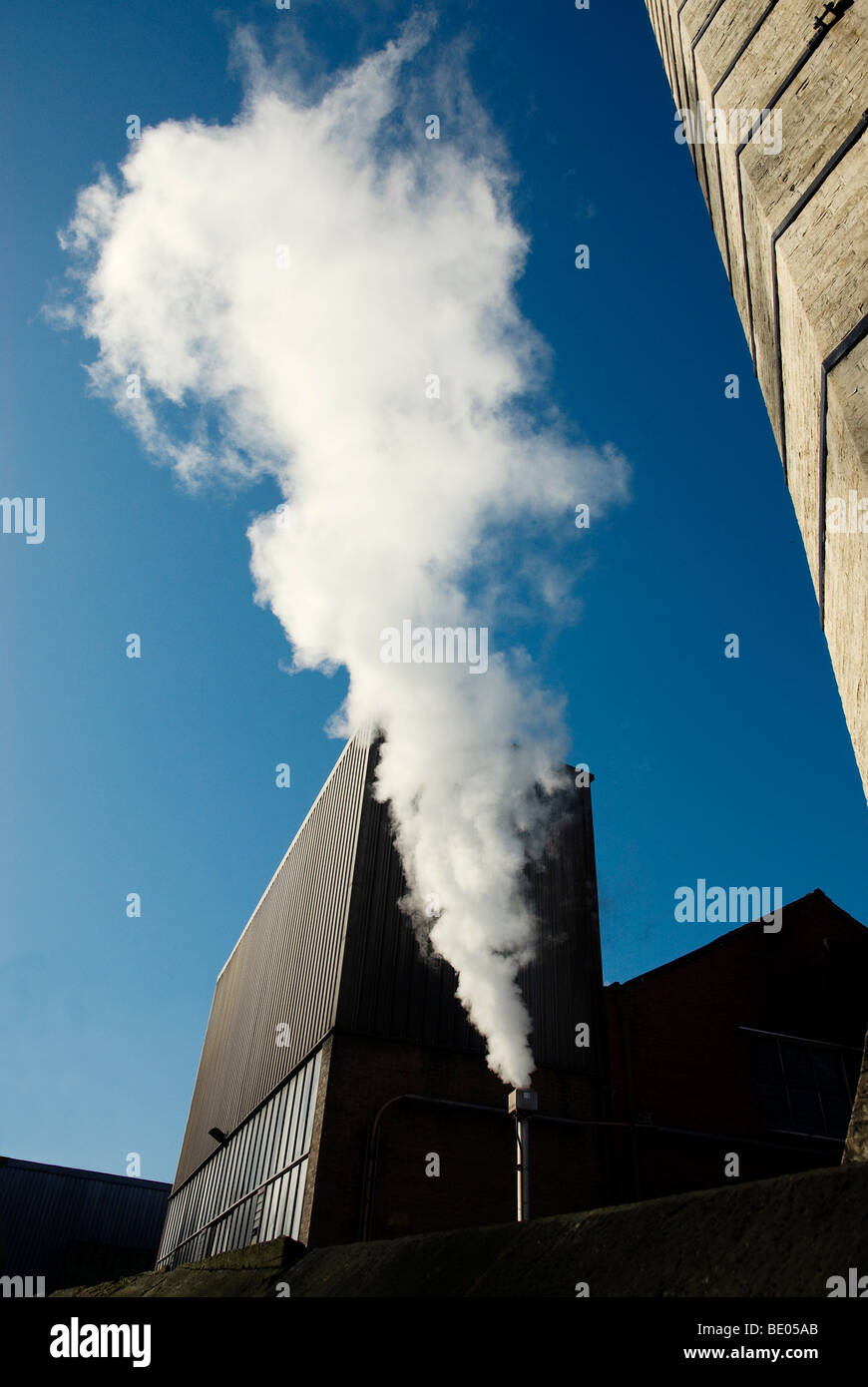 Steam coming out of pipe next to factory buildings against deep blue sky - Stock Image