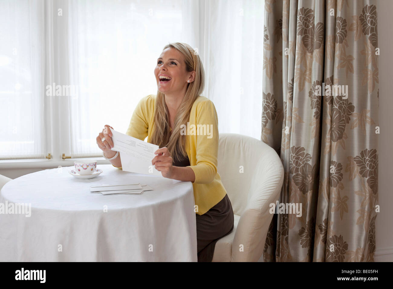 Young woman happy about good news - Stock Image