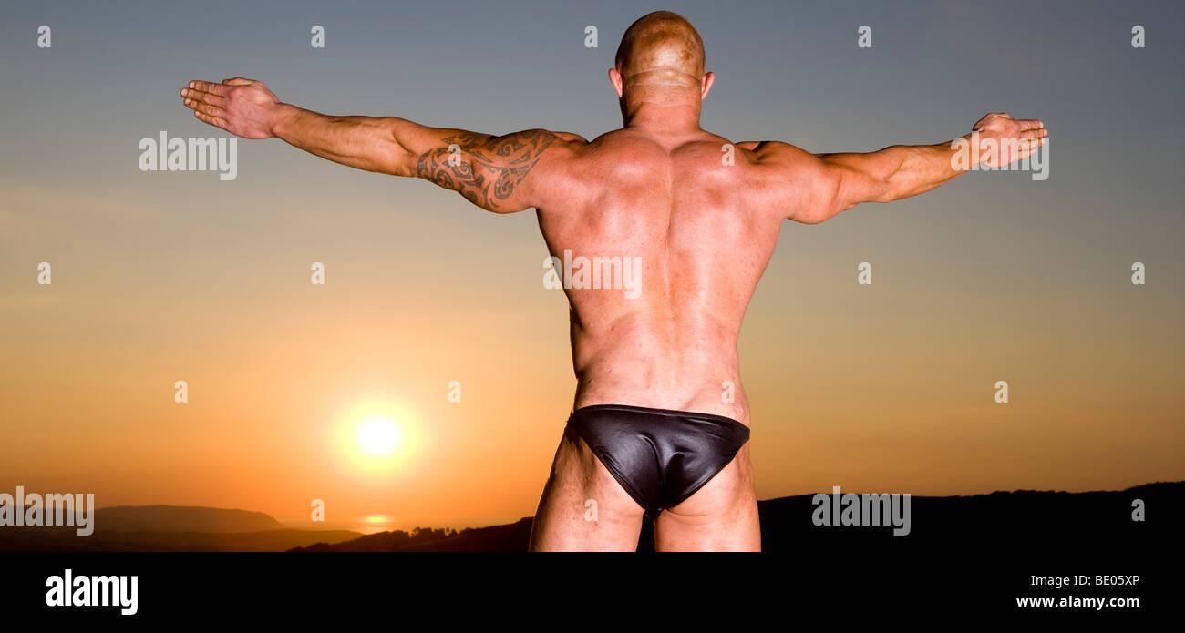 Bodybuilder Poses at Sunset. - Stock Image