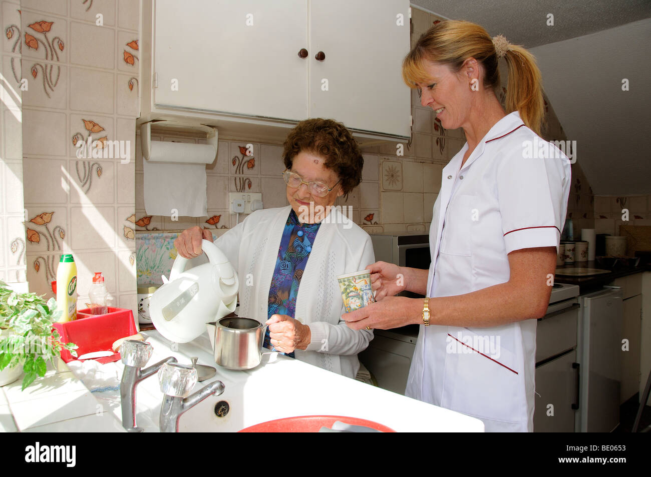 Elderly woman in kitchen with a social services carer pouring boiling water into a teapot - Stock Image
