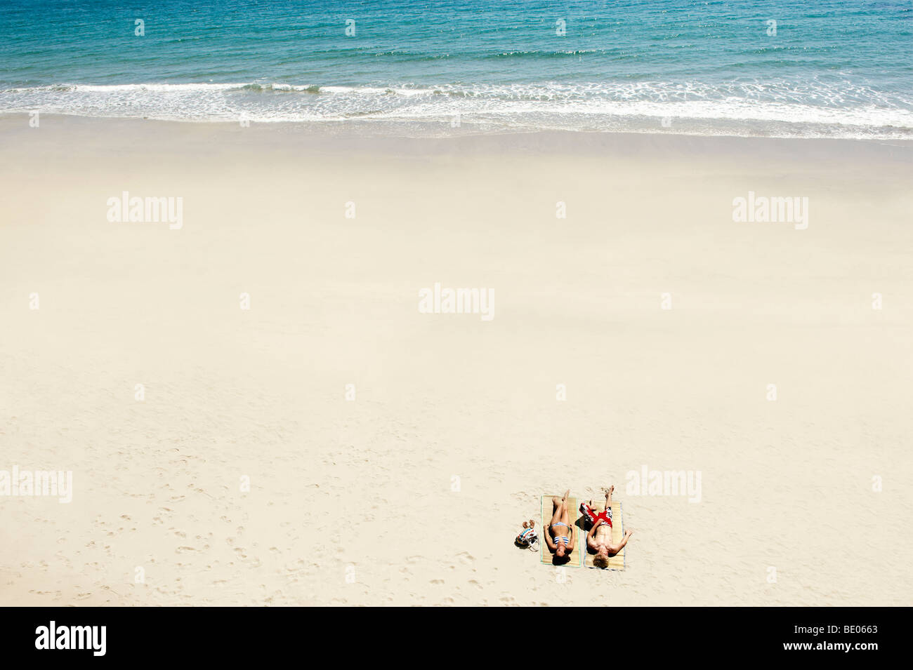 Couple sunbathing on white sandy beach - Stock Image