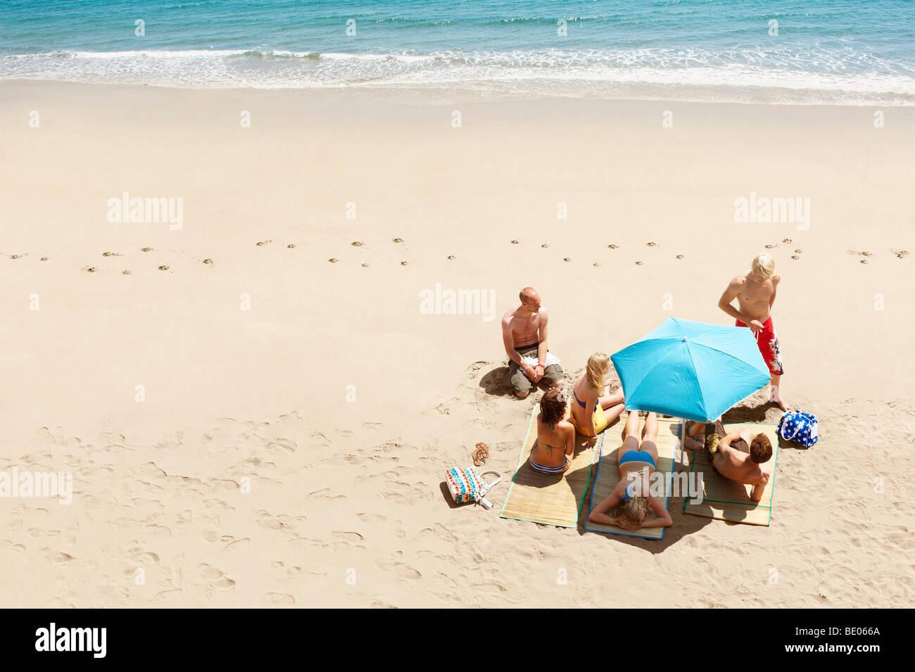 group of people sunbathing on beach - Stock Image