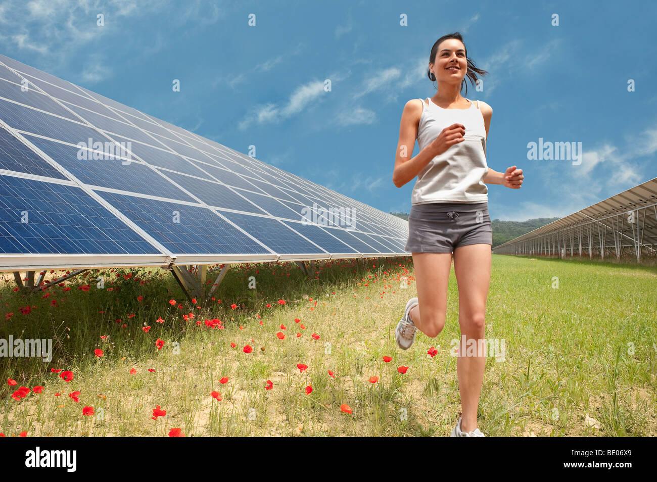 woman jogging along solar panel - Stock Image