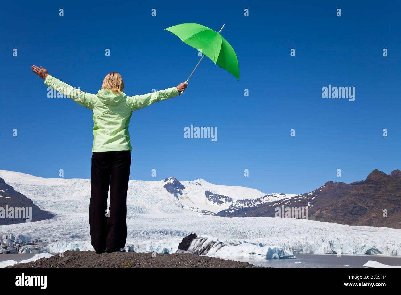 Environmental concept shot of a woman dressed in green with a green umbrella standing arms outstretched in front - Stock Image