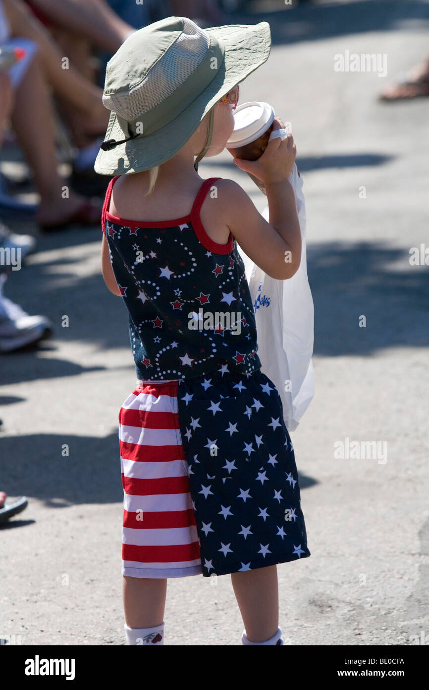 Child wearing a patriotic outfit while watching a 4th of July parade in Cascade, Idaho, USA. - Stock Image