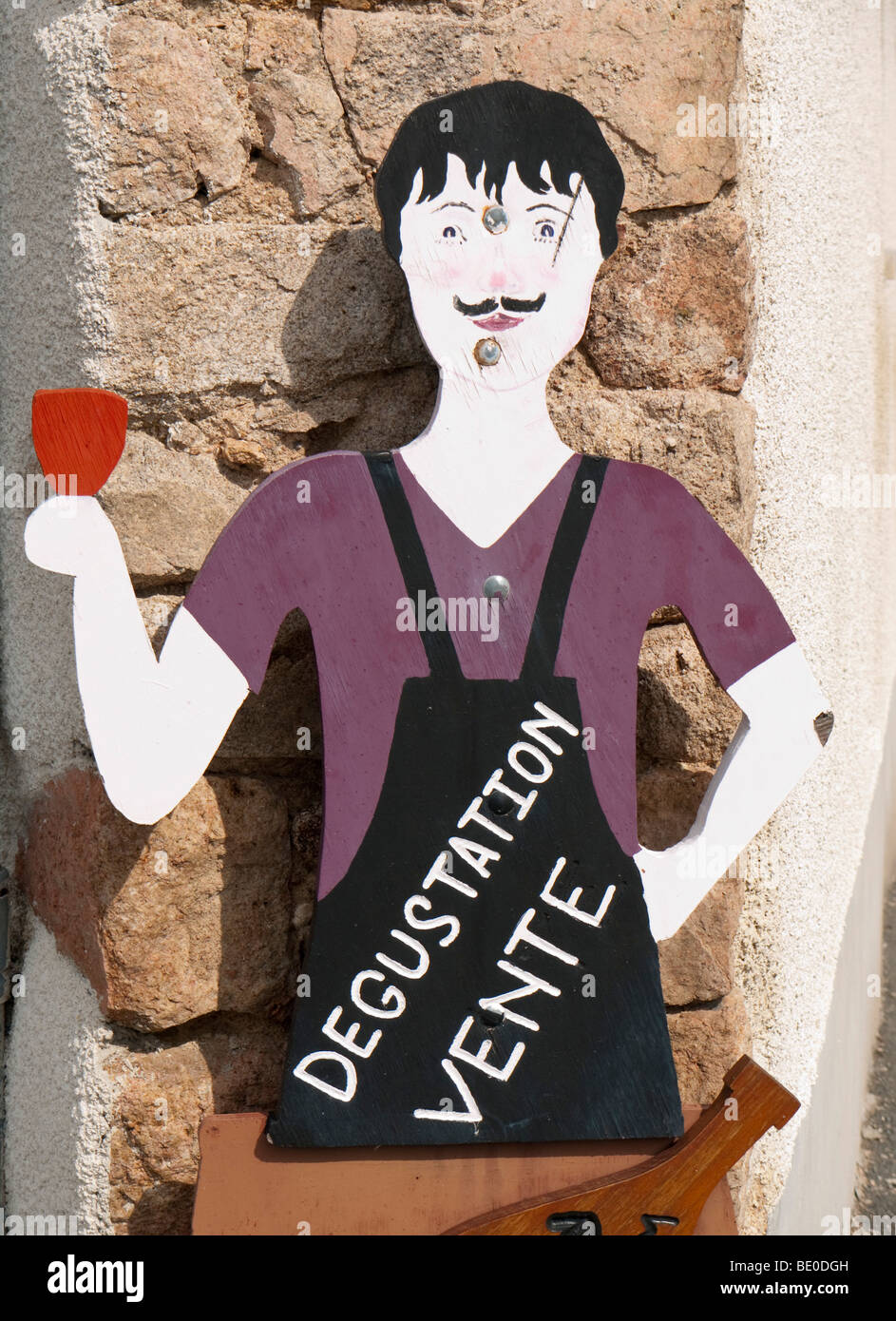 A wooden figure resembling a vintner advertises the renowned Beaujolais wine of Fleurie. - Stock Image