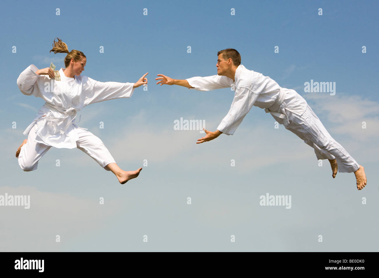 Young woman holding cash fighting young man as they fly through the air - Stock Image