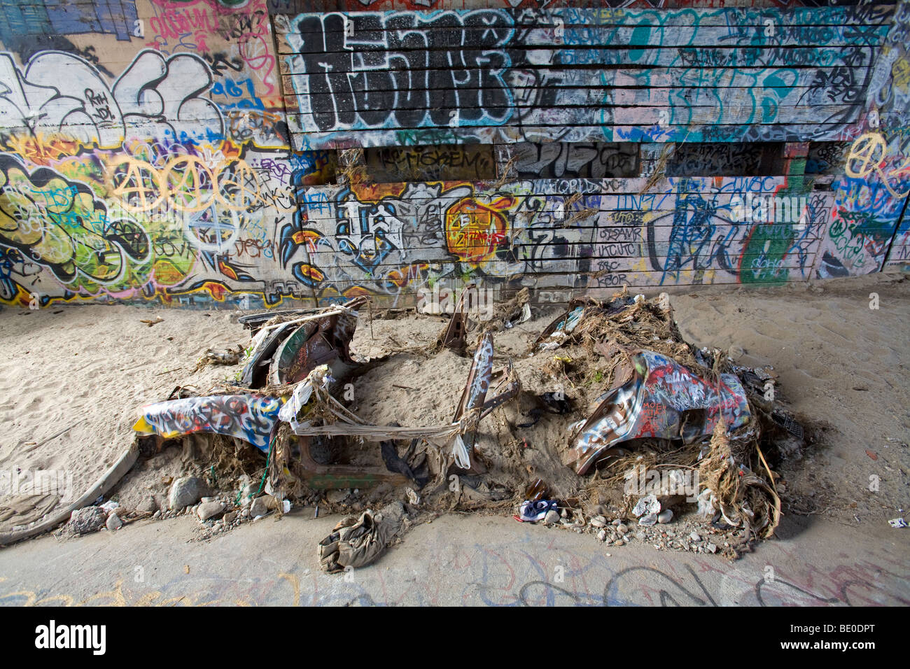 Abandoned car and graffiti underneath bridge in the Los Angeles River, California, USA. - Stock Image
