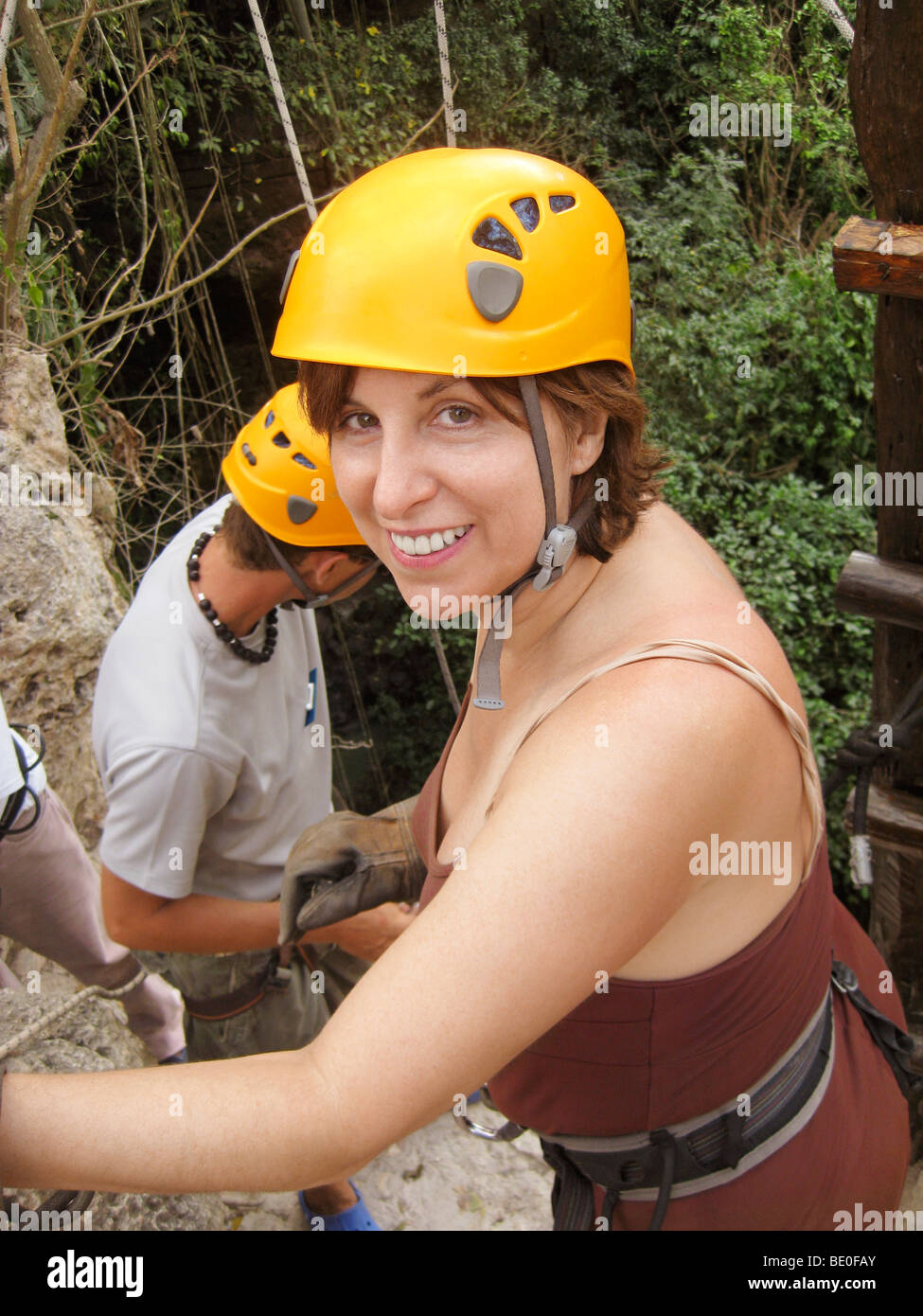Middle aged adult woman doing outdoor activities waiting for a zip line and wearing a helmet - Stock Image