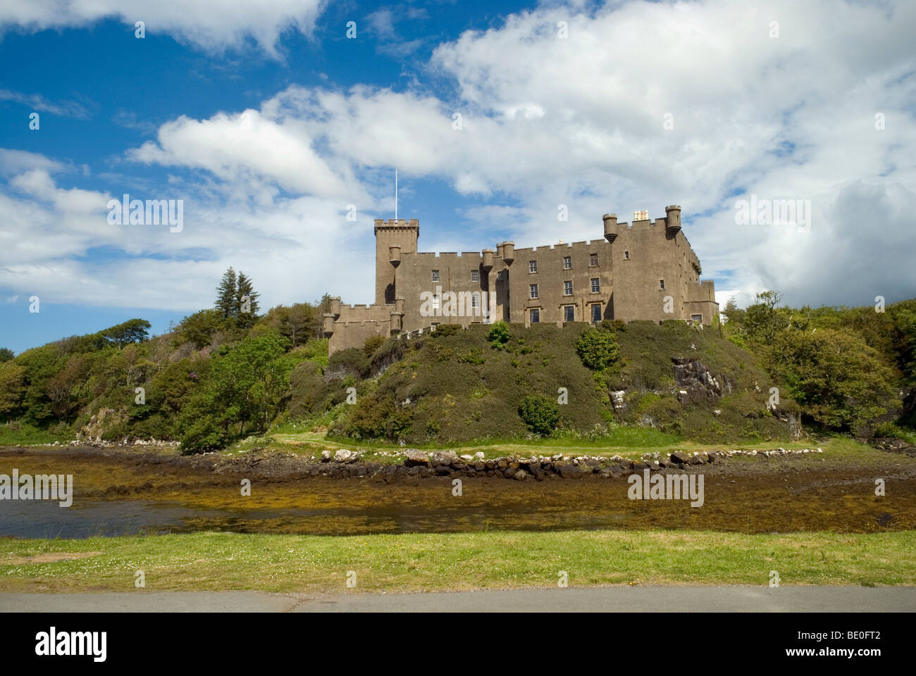 Dunvegan castle on a fine day with blue sky but some cloud seen from across a waterway inlet from the loch - Stock Image