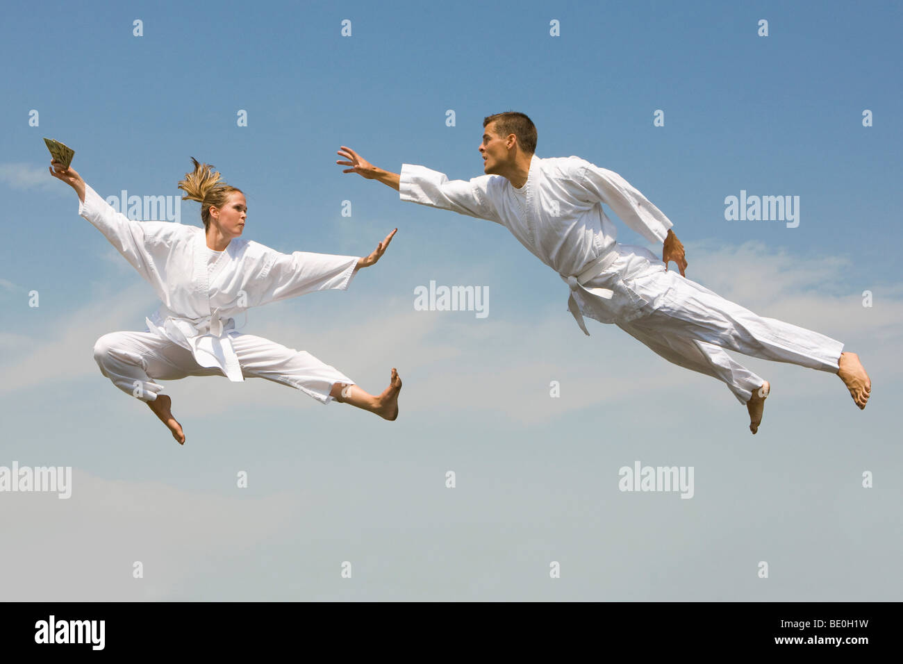 Young woman holding cash evading young man as they fly through the air - Stock Image