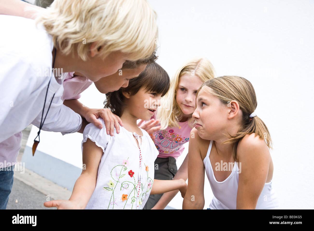 Young schoolgirl in the schoolyard, talking with older children Stock Photo