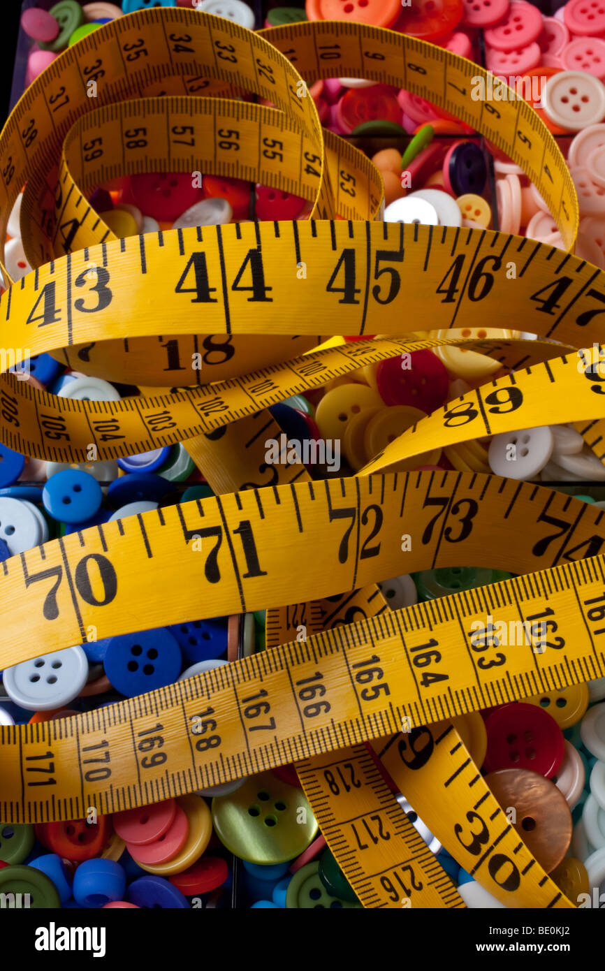 Yellow tape measure on buttons - Stock Image