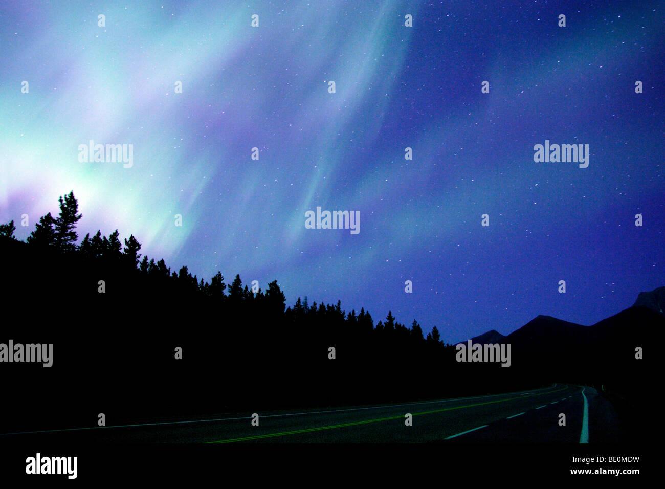 Northern Lights above highway at dusk - Stock Image