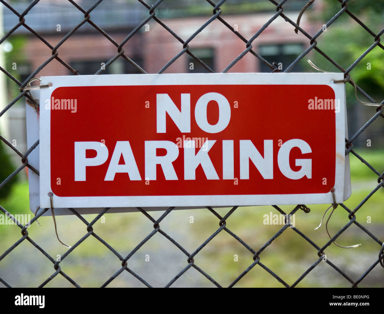 A No Parking sign hunging on a fence. - Stock Image