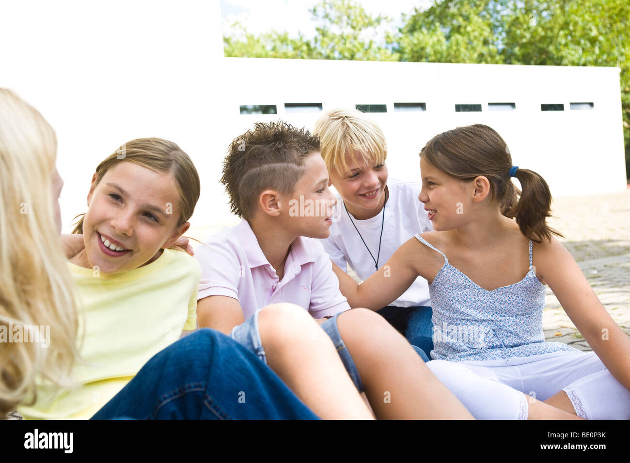 Five pupils talking in the schoolyard - Stock Image