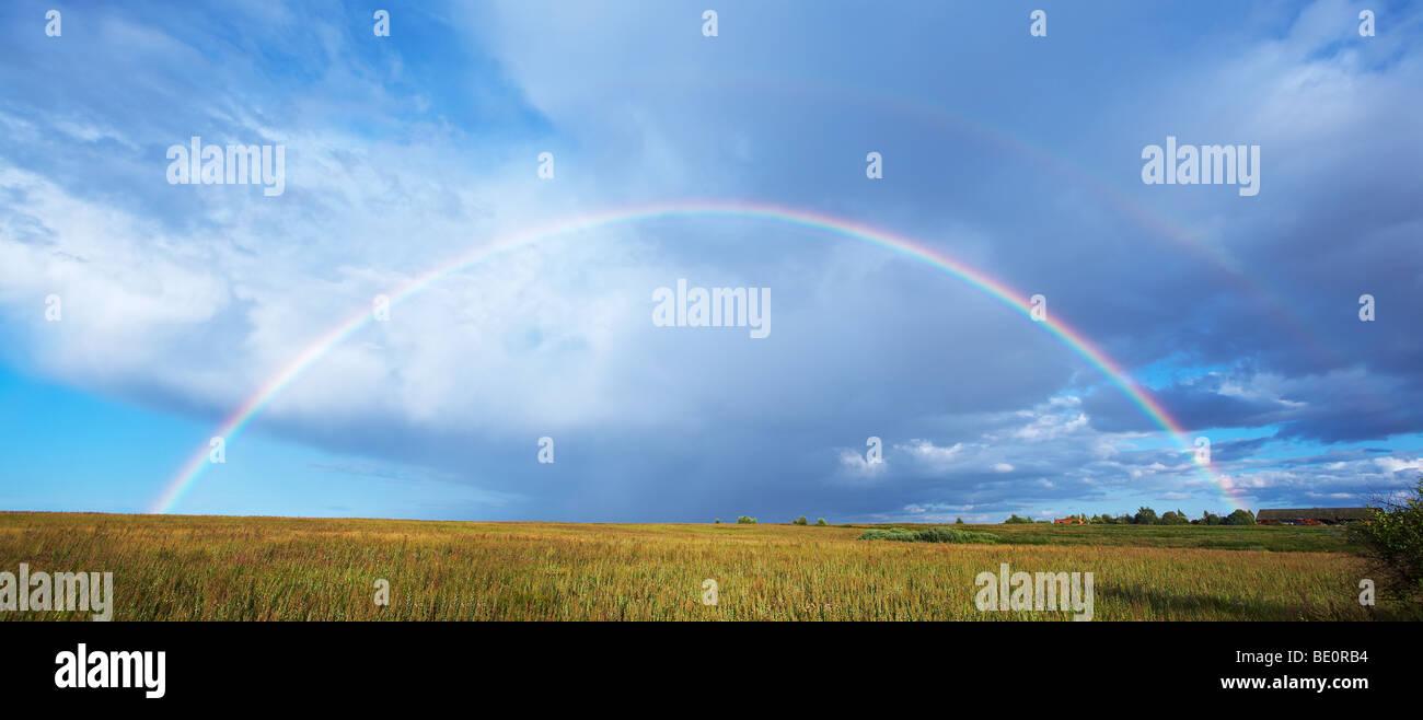 Rainbow over autumn grass field - Stock Image