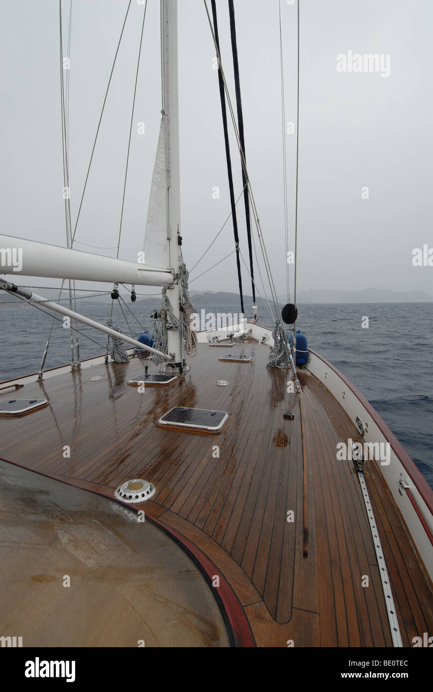 wooden sailboat sailig in the rain - Stock Image