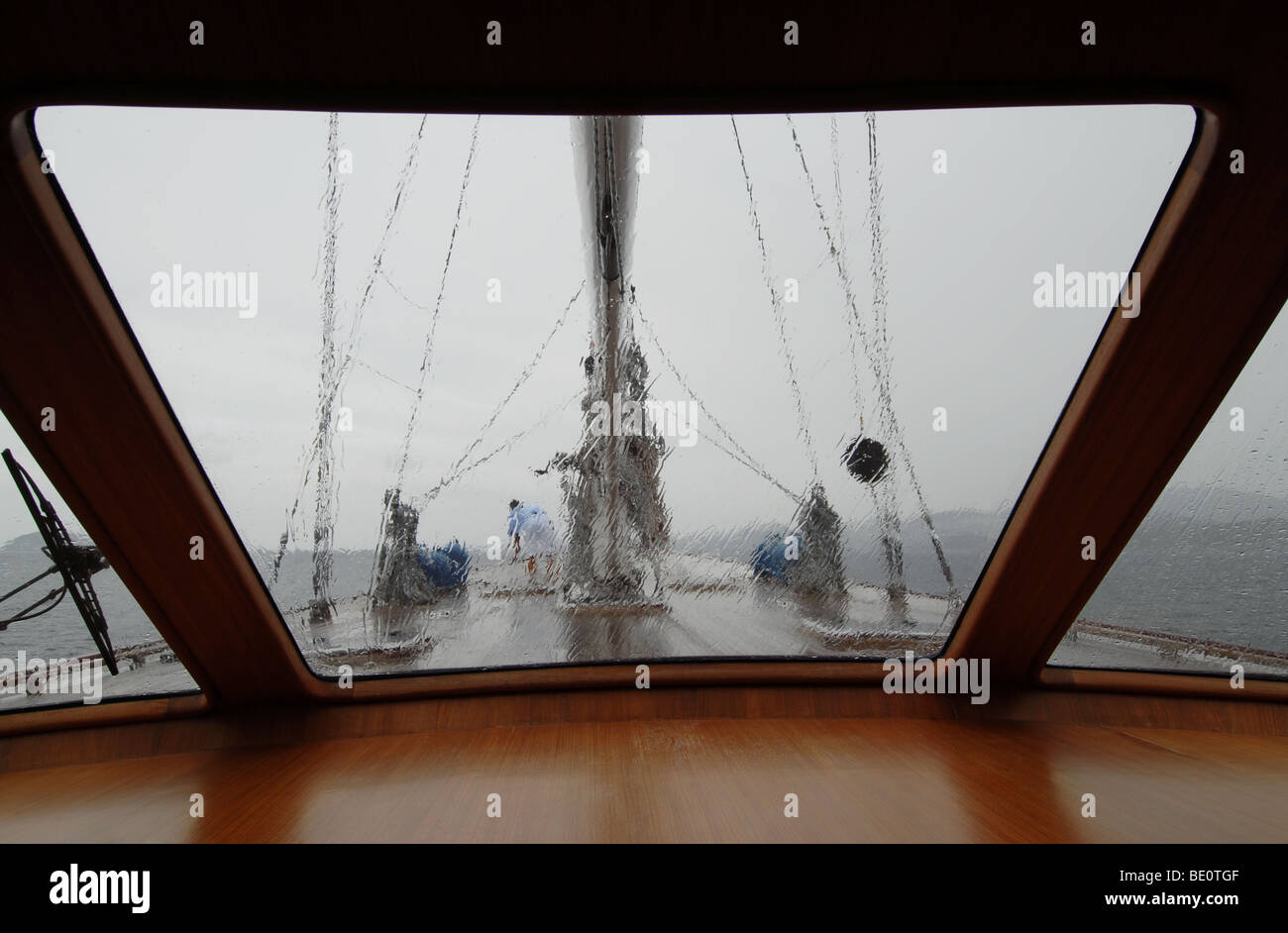 wooden sailboat sailing in the rain - Stock Image