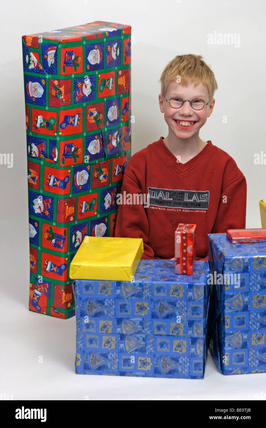 portrait of a young boy surrounded by Christmas presents - Stock Image