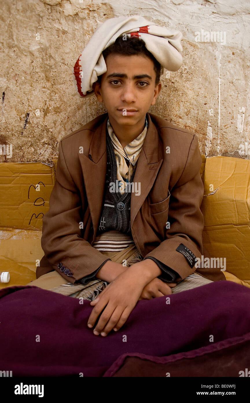 A portrait of a teenage Yemeni khat merchant sitting in the khat souq of Old Sana'a, Yemen. - Stock Image