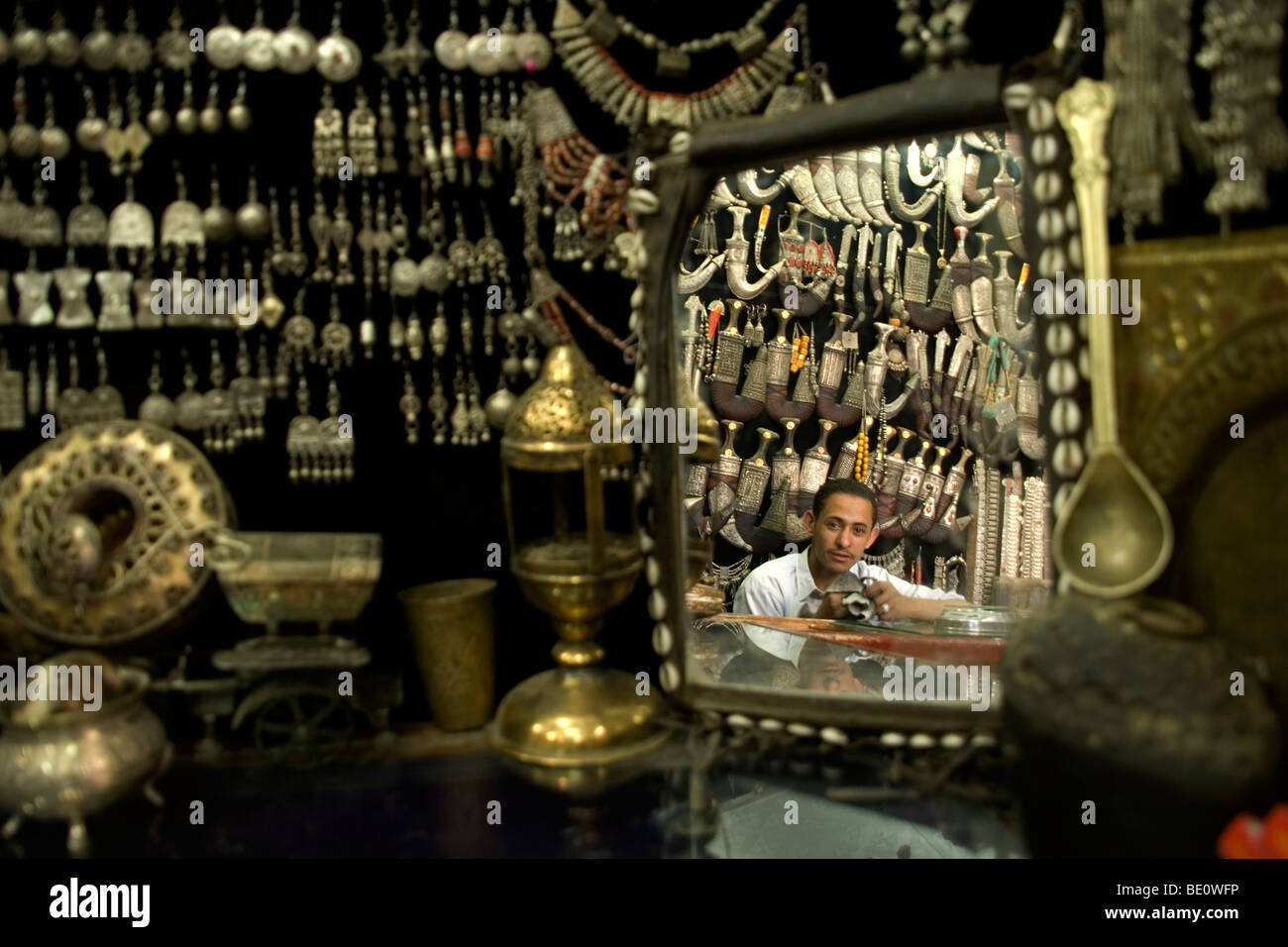 A jewelery vendor seen in the reflection of a mirror among his wares in a store in the old city of Sana'a, Yemen. - Stock Image