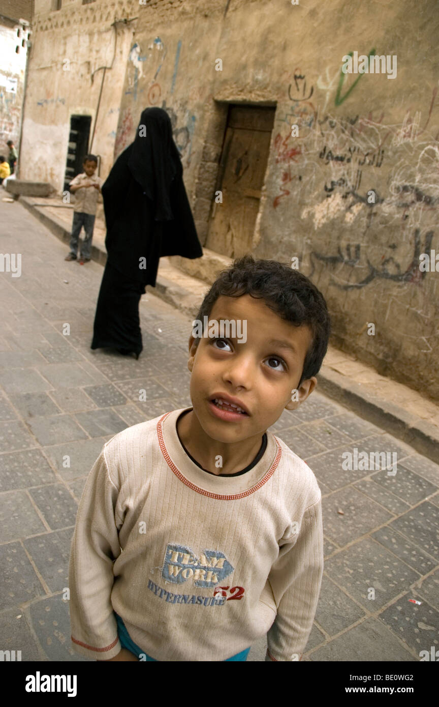 A Yemeni boy playing in the streets of the old city of Sana'a, with a woman dressed in a niqab, walking behind - Stock Image