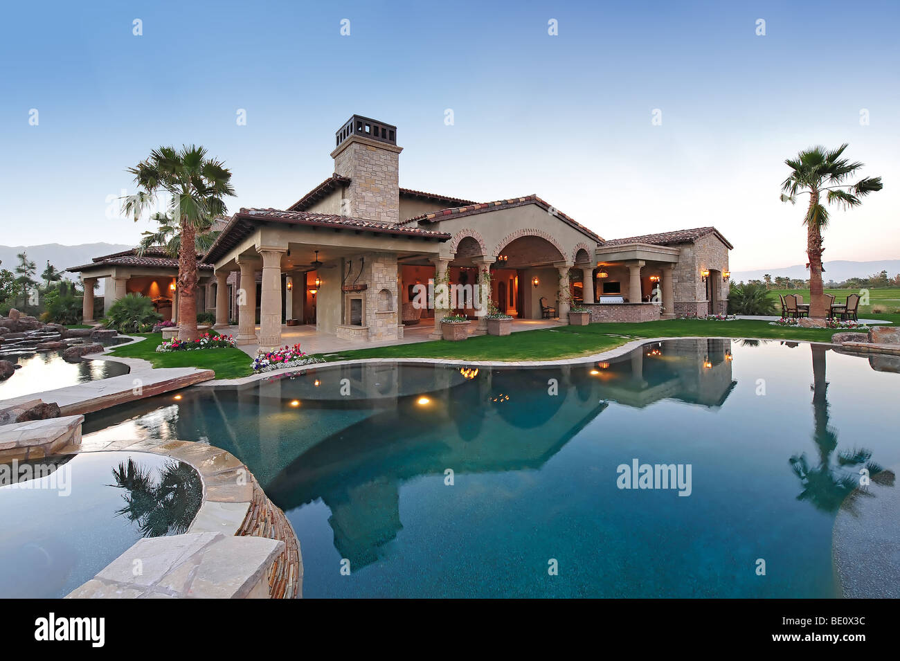 View across swimming pool of massive luxury home at dusk Stock Photo