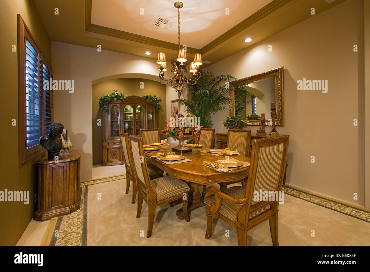 Elegant traditional furnished dining room in warm tones with shuttered windows - Stock Image