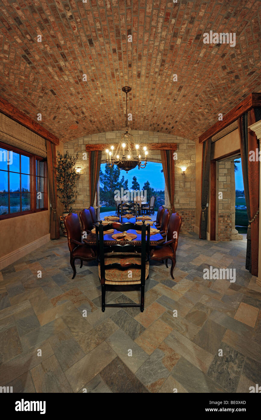 Romantic dining room with coved brick ceiling is shown at night with open French doors - Stock Image
