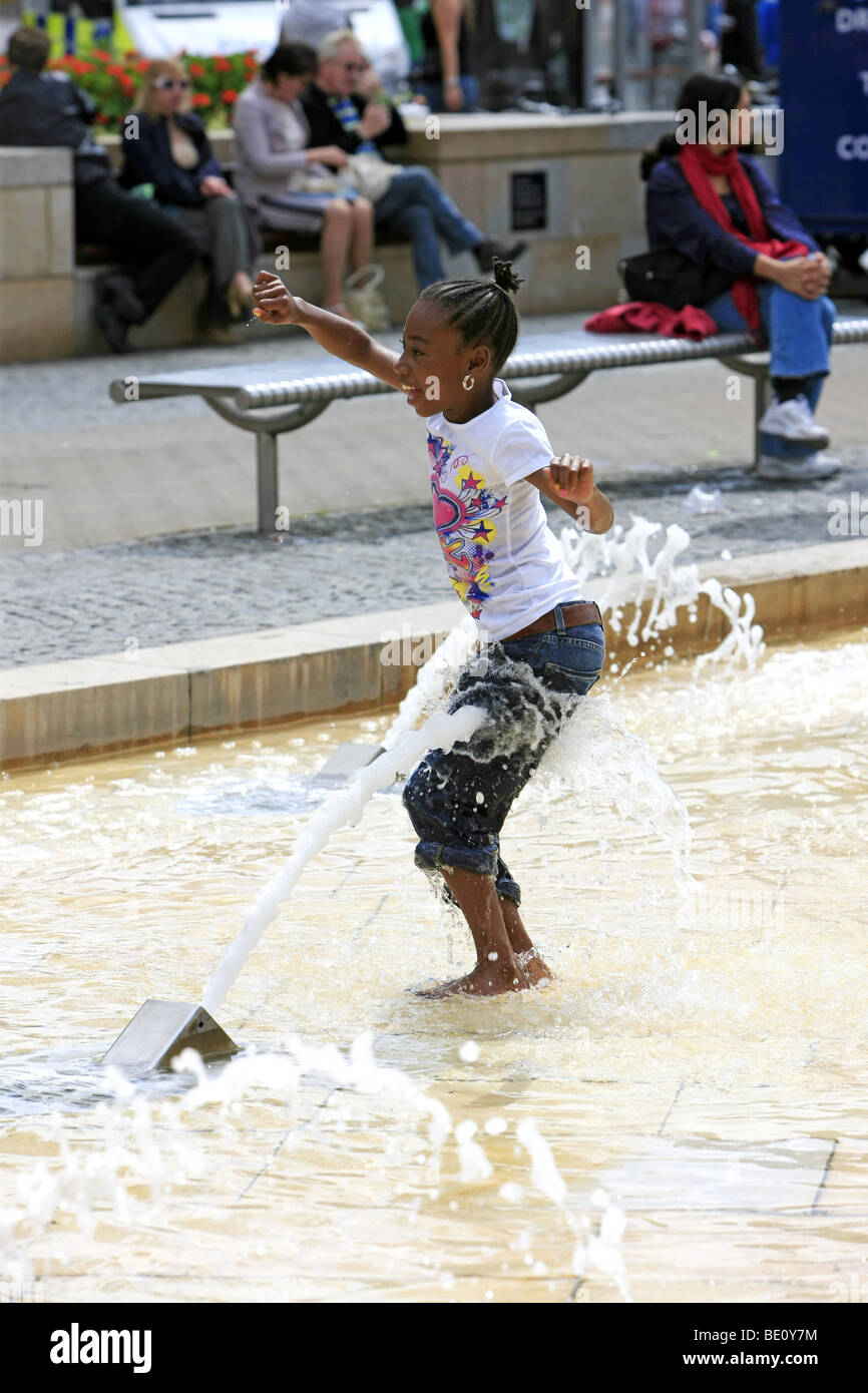 Black children playing with the water fountains on a hot summers day - Stock Image