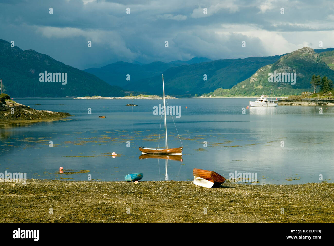 Boats resting on the shores of Plockton in the north west highlands of scotland, with calm waters and a storm brewing - Stock Image