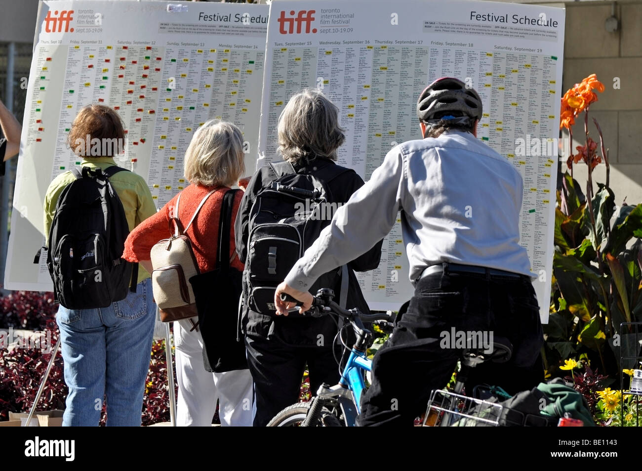 People, passers by studying the TIFF(Toronto International Film Festival Schedules) - Stock Image