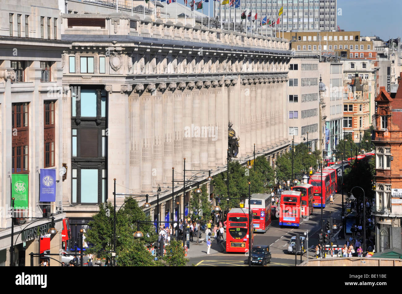 Oxford Street frontage of Selfridges department store with long queue of double decker red London buses - Stock Image
