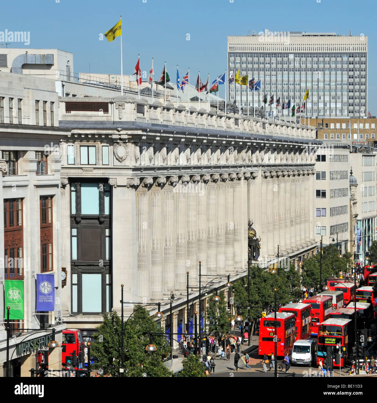 Oxford Street frontage of Selfridges department store with flags flying at roof top level & red London buses West End London England UK Stock Photo