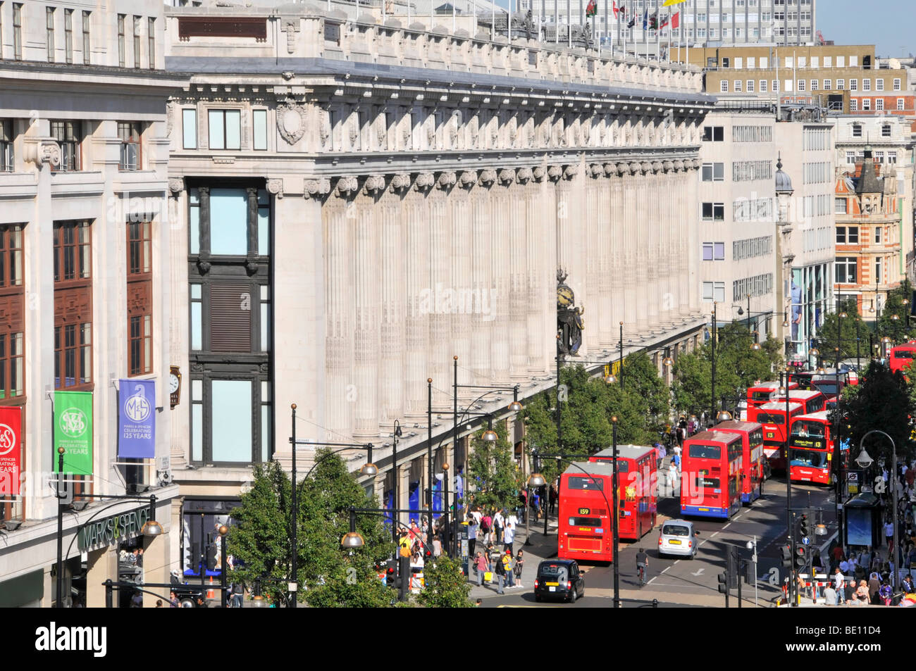 Oxford Street frontage of Selfridges department store with queue of double decker red London buses West End London - Stock Image