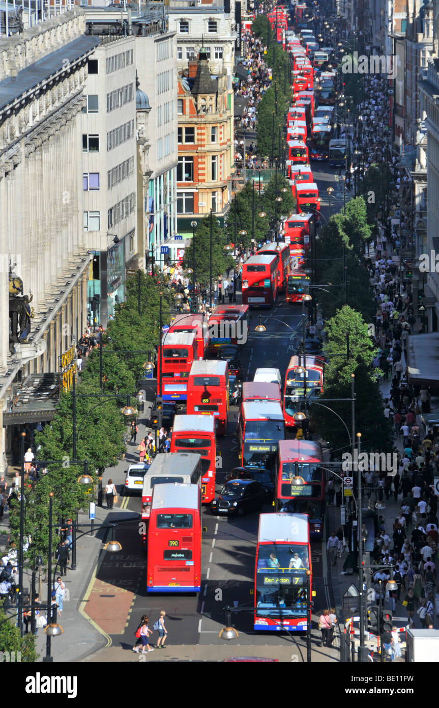 Looking down on busy UK Oxford Street with shoppers &aerial views of long queues of double decker red London - Stock Image