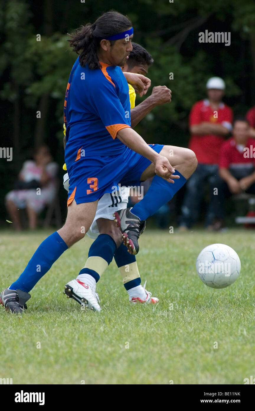 Two soccer players battle for possession of the ball. - Stock Image